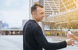 Mano dell'uomo che dà bottiglia di acqua potabile dopo avere eseguito esercizio alla capitale fotografie stock libere da diritti