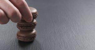 Mano dell'uomo che impila i macarons del cioccolato sul bordo dell'ardesia Fotografie Stock Libere da Diritti