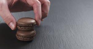 Mano dell'uomo che impila i macarons del cioccolato sul bordo dell'ardesia Fotografia Stock