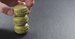 Mano dell'uomo che impila i macarons del pistacchio sul bordo dell'ardesia Fotografie Stock Libere da Diritti