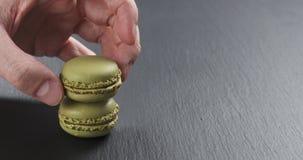 Mano dell'uomo che impila i macarons del pistacchio sul bordo dell'ardesia Fotografia Stock