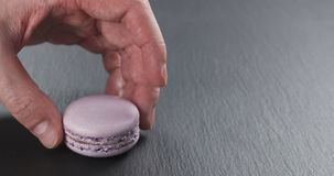 Mano dell'uomo che impila i macarons della lavanda sul bordo dell'ardesia Fotografie Stock Libere da Diritti