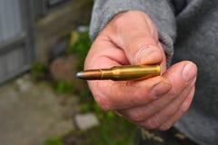 Mano dell'uomo che mostra 7 pallottola delle munizioni di 62 calibri Fotografie Stock