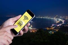 Mano dell'uomo che per mezzo del taxi di chiamata dello smartphone dallo smartphone di applicazione Fotografie Stock