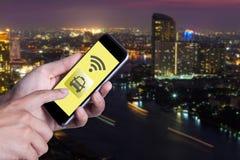 Mano dell'uomo che per mezzo del taxi di chiamata dello smartphone dallo smartphone di applicazione Immagine Stock