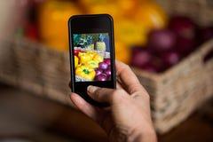 Mano dell'uomo che prende foto delle verdure Fotografia Stock Libera da Diritti