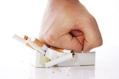 Mano dell'uomo che schiaccia le sigarette Fotografia Stock