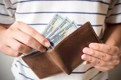Mano dell'uomo che tiene la fattura di valuta americana del dollaro americano con soldi Fotografia Stock