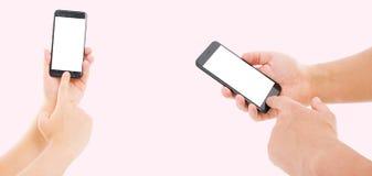Mano dell'uomo che tiene lo smartphone nero con lo schermo in bianco e la struttura moderna meno progettazione su fondo rosa immagini stock