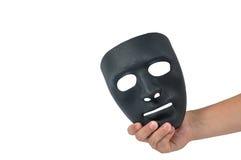 Mano dell'uomo che tiene maschera nera, comportamento umano Fotografia Stock