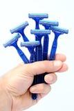 Mano dell'uomo che tiene sette rasoi blu a gettare Fotografia Stock