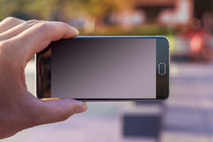 Mano dell'uomo che tiene smartphone contemporaneo Fotografia Stock Libera da Diritti