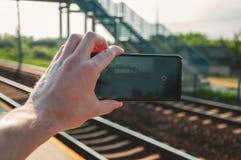 Mano dell'uomo che tiene uno smartphone e che prende una fotografia della stazione ferroviaria durante la molla, mezzogiorno fotografie stock