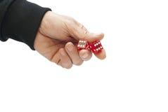Mano dell'uomo con due dadi rossi Fotografie Stock