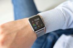 Mano dell'uomo con l'orologio di Apple nella casa Fotografia Stock