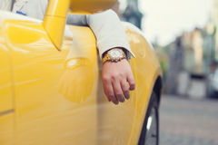 Mano dell'uomo con l'orologio dorato in automobile Fotografia Stock Libera da Diritti