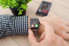 Mano dell'uomo con l'orologio e la telefonata di Apple sullo schermo Immagine Stock Libera da Diritti