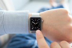 Mano dell'uomo con l'orologio ed il quadrante di Apple sullo schermo Immagini Stock