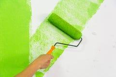 Mano dell'uomo con la spazzola del rullo che dipinge colore verde sulla parete Immagini Stock