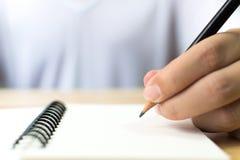 Mano dell'uomo con scrittura della matita sul taccuino Fotografie Stock