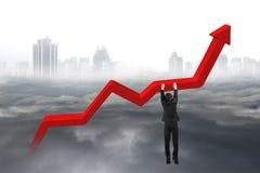 Mano dell'uomo d'affari che appende sul grafico rosso di tendenza con cityscap nuvoloso Immagine Stock