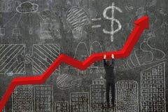 Mano dell'uomo d'affari che appende sul grafico rosso di tendenza con la parete di scarabocchi Immagine Stock Libera da Diritti