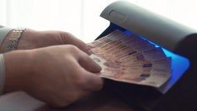Mano dell'uomo d'affari che controlla cinque mila banconote della rublo sul rivelatore della luce UV archivi video