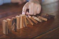 Mano dell'uomo d'affari che ferma effetto di domino di legno di caduta dal rovesciato da continuo o rischio, strategia e riuscito fotografia stock libera da diritti