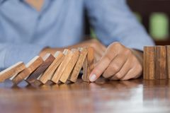 Mano dell'uomo d'affari che ferma effetto di domino di legno di caduta dal rovesciato da continuo o rischio, strategia e riuscito immagini stock