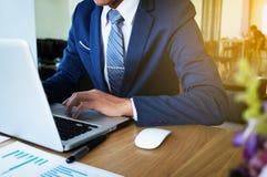 Mano dell'uomo d'affari che funziona con il nuovo computer moderno e l'affare s immagini stock