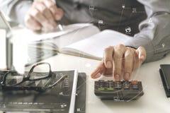 mano dell'uomo d'affari che funziona con le finanze circa costo ed il calcolatore Immagini Stock