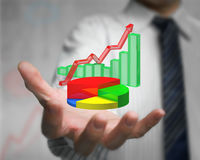 Mano dell'uomo d'affari che giudica infographics 3d sovrapposto Immagine Stock