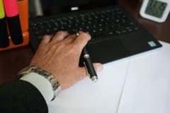 Mano dell'uomo d'affari che scrive su un computer portatile fotografie stock