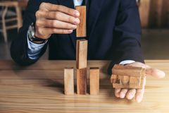 Mano dell'uomo d'affari che sistema impilando sviluppo di legno dei blocchi As Immagini Stock