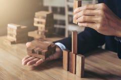 Mano dell'uomo d'affari che sistema impilando sviluppo di legno dei blocchi As Fotografia Stock