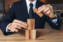 Mano dell'uomo d'affari che sistema impilando sviluppo di legno dei blocchi As Immagini Stock Libere da Diritti