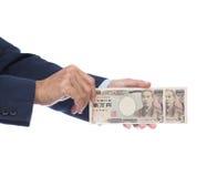 Mano dell'uomo d'affari che tiene banconota giapponese Immagine Stock