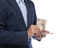 Mano dell'uomo d'affari che tiene banconota giapponese Fotografie Stock Libere da Diritti