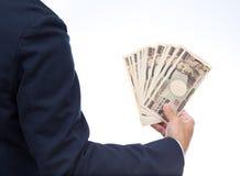 Mano dell'uomo d'affari che tiene banconota giapponese Fotografia Stock Libera da Diritti