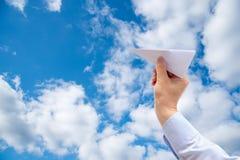 Mano dell'uomo d'affari che tiene l'aereo della carta sul fondo del cielo immagini stock libere da diritti