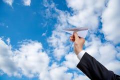 Mano dell'uomo d'affari che tiene l'aereo della carta sul fondo del cielo fotografia stock