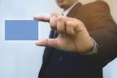 Mano dell'uomo d'affari che tiene la carta blu immagine stock libera da diritti