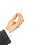 Mano dell'uomo d'affari che tiene una lampadina Fotografie Stock Libere da Diritti