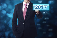 Mano dell'uomo d'affari che tocca un numero di 2017 bottoni Fotografia Stock Libera da Diritti