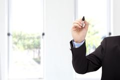 Mano dell'uomo d'affari con la penna pronta a scrivere qualcosa immagine stock
