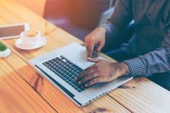 Mano dell'uomo d'affari facendo uso del computer portatile in caffè del caffè Immagini Stock Libere da Diritti