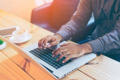 Mano dell'uomo d'affari facendo uso del computer portatile in caffè del caffè Fotografia Stock Libera da Diritti
