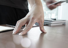 Mano dell'uomo d'affari facendo uso del computer portatile e del telefono cellulare Immagini Stock