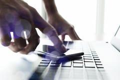 Mano dell'uomo d'affari facendo uso del computer portatile e del telefono cellulare Fotografie Stock Libere da Diritti