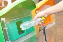 Mano dell'uomo del primo piano che getta bottiglia di acqua di plastica vuota nei rifiuti Ricicli lo scomparto immagini stock libere da diritti